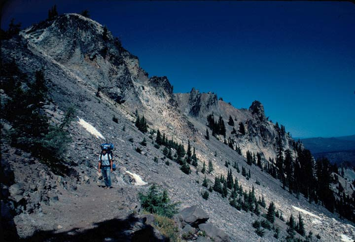 A lone hiker traversing a narrow alpine trail along the face of a rocky slope, dotted with sparse pine trees.
