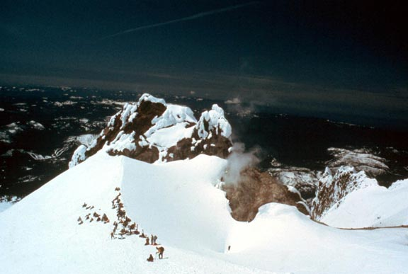 Looking down snow covered summit ridge, to a large group of climbers gathered on the snow below.