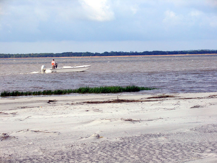 Looking out over the white-sand beach to a lone law enforcement officer in a small white boat, patroling the shoreline.