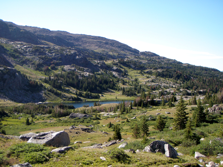 A field scattered with boulders, trees and shrubs slope down to a lake sitting at the base of steep sloping hills.