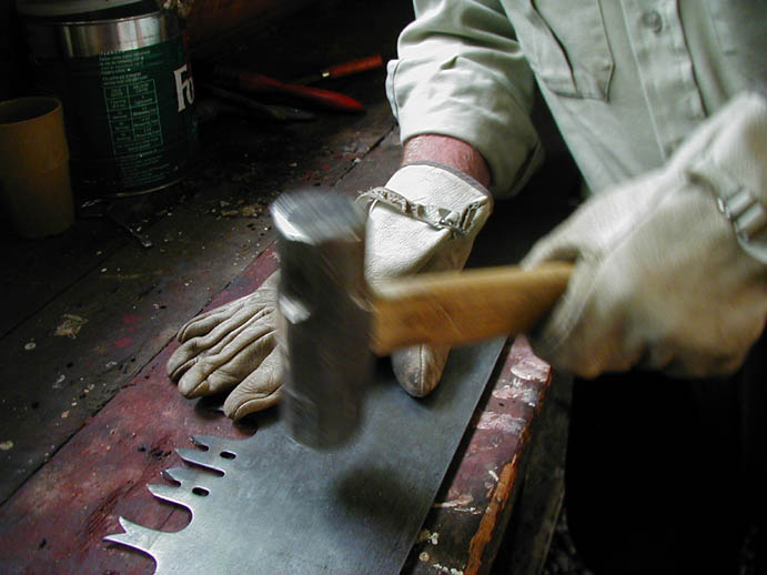 A close-up of a man using a large hammer to straighten the blade of a hand saw.