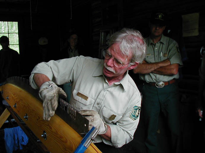 A man giving a demonstration on proper care of a large hand saw.