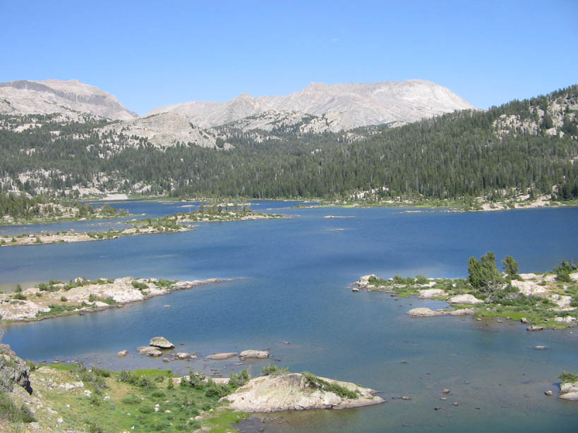 A large blue lake, dotted with small rock islands, and surrounded by low forested hills.