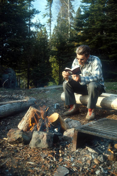 A camper reads near a fire in the Cherokee Lake Island camp.