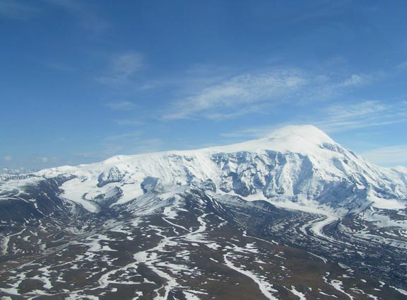 A massive snow-covered slope leading up to a high summit, looming high over the valley below.