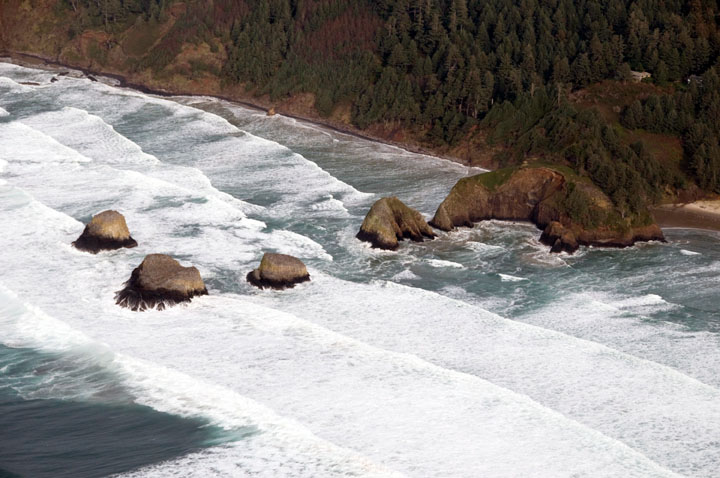 An aerial view of small rock islands stretching out into an advancing row of foaming white swells.