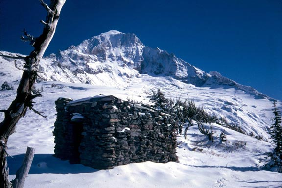 A small stone shelter surrounded by snow on an open slope, leading up to a jagged summit far beyond.