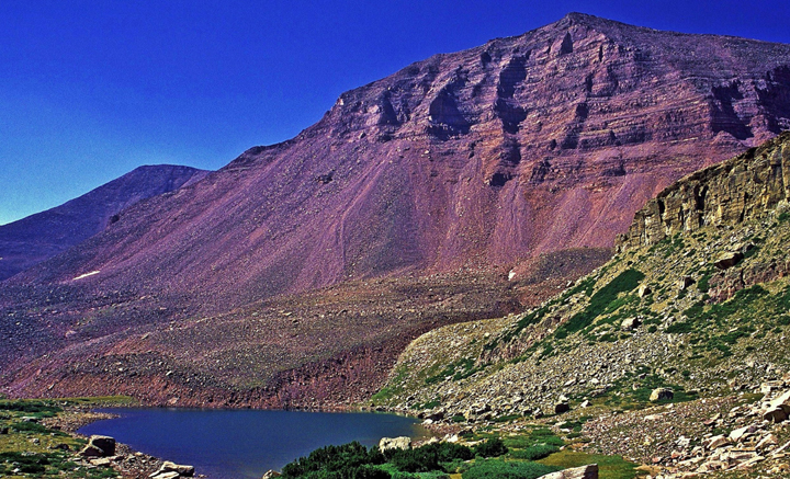 A clean blue mountain lake surrounded by rocky slopes with a peak looming behind it.