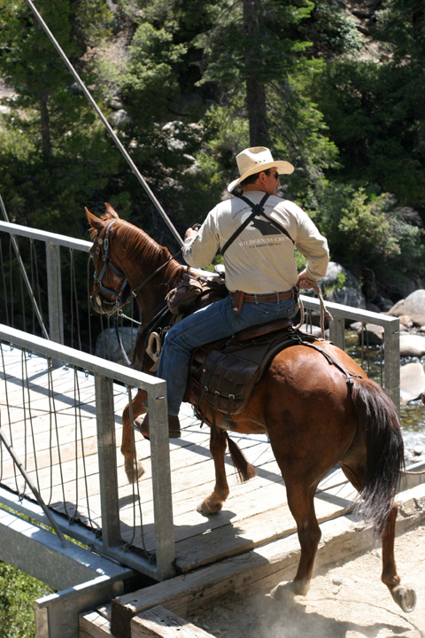 A packer on horseback enters the Sheep Crossing Bridge. When a packer gets to the Sheep Crossing Bridge, he keeps moving or the stock start a rodeo. A pack string hauls heavy loads and supplies for wilderness rangers and trail crews. North Fork of San Joaquin River, Ansel Adams Wilderness.