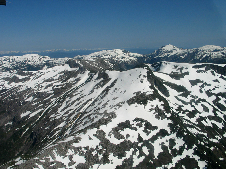 Large snow-patched mountain peaks viewed from above.