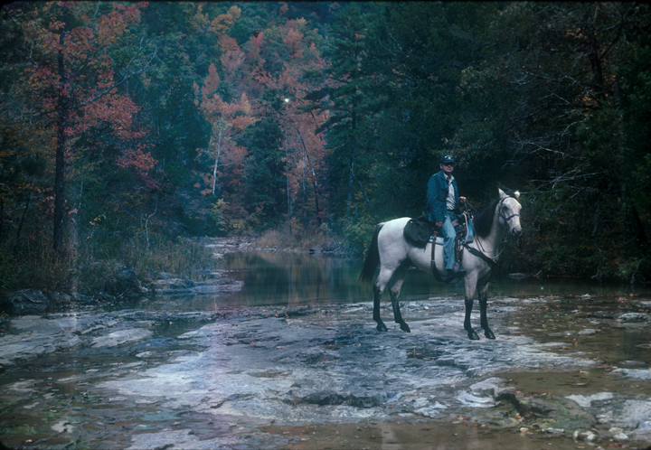 A man and horse cross a riverbed.