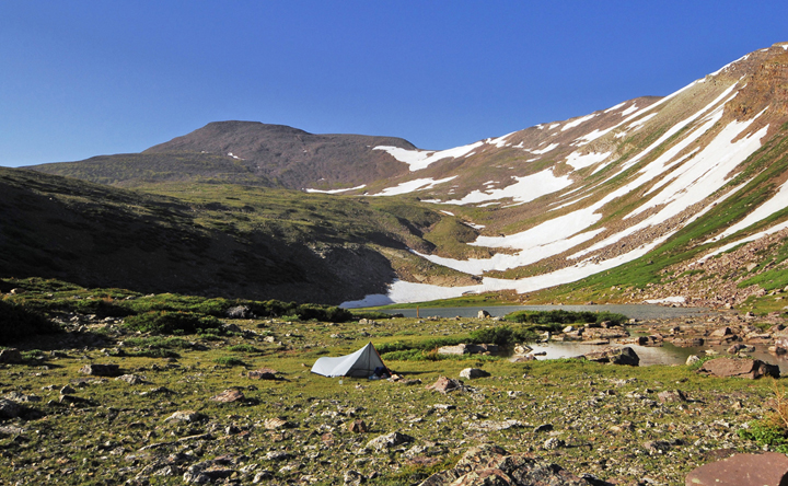 Large, rounded, snow-spotted mountain peaks swoop down to a small lake and a rocky meadow.