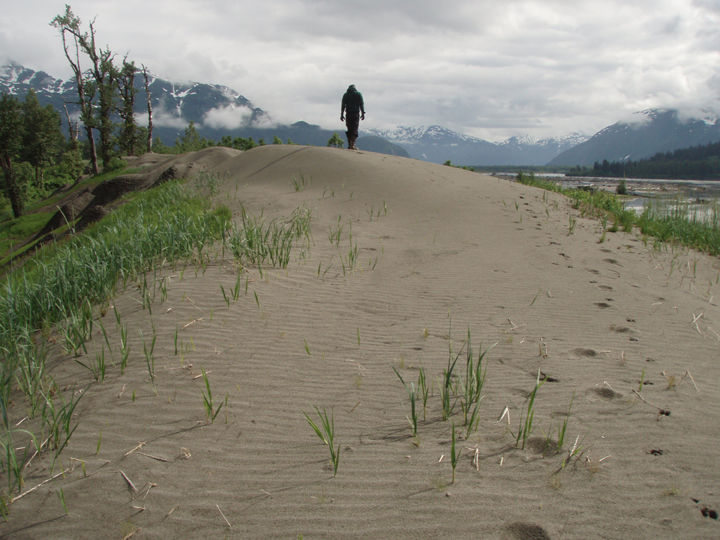 A lone hiker walks across a small sand dune next to  wide river.