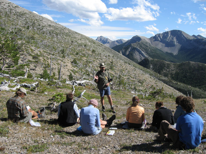 A staff member speaks to a group of students who sit while the staff member stands. Taken during the University of Montana's Wilderness and Civilization Field Studies Fall 2008 Trek.