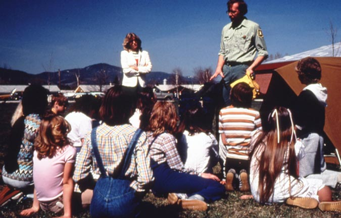 A park ranger speaking to a group of students, sitting on the ground near a campsite.