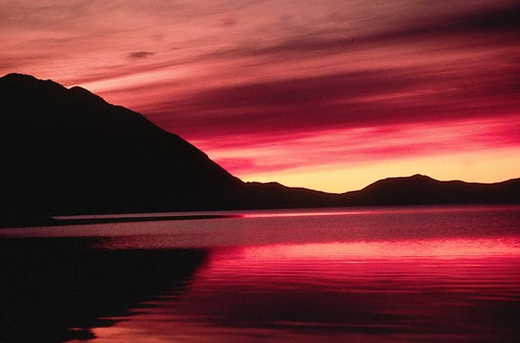 An abstract sunrise, deep red streaks across the sky above the black sillohouettes of surrounding mountains, reflected from the surface of an open lake.