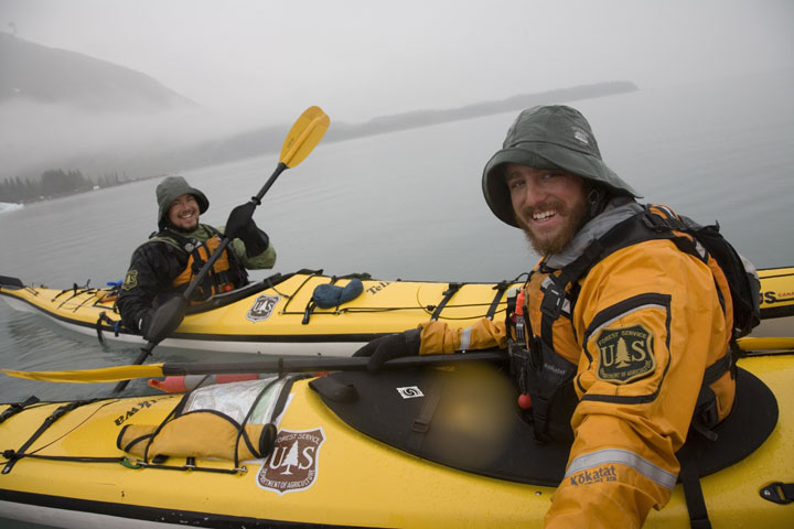 Two male Forest Service kayak rangers in bright yellow kayaks smile for the camera in a misty Inlet.