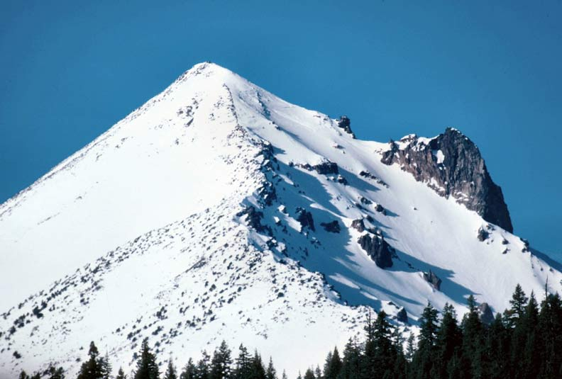 A close-up of a high summit in winter, heavy snow cover drifting around large rock outcroppings near the summit.