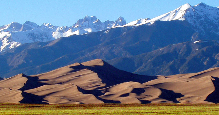 Wind sculpted sand dunes rise above the grass, as towering snowcapped mountains loom in the background.