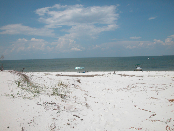 The sand is white and the ocean is gray under a brilliant blue sky.  A few umbrellas are on the beach near a beached boat.