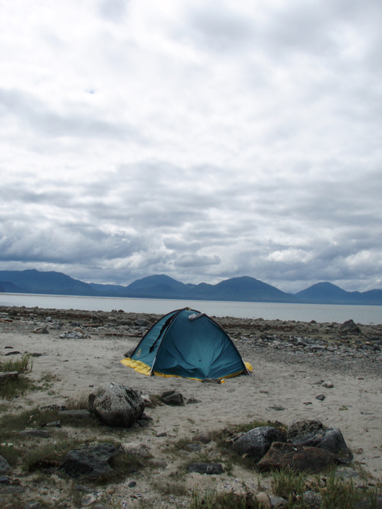 A dark blue tent sits on the sandy shore of a large bay.