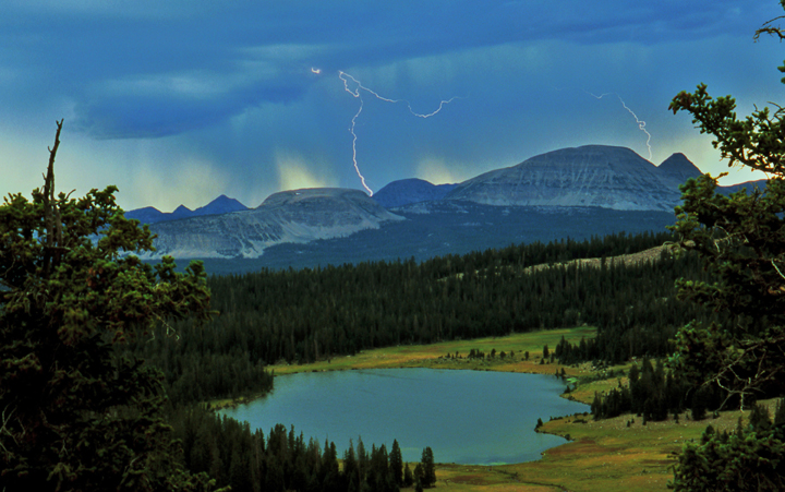 Lightening flashes through dark storm clouds sitting above a mountain peak with a large lake in the foreground.
