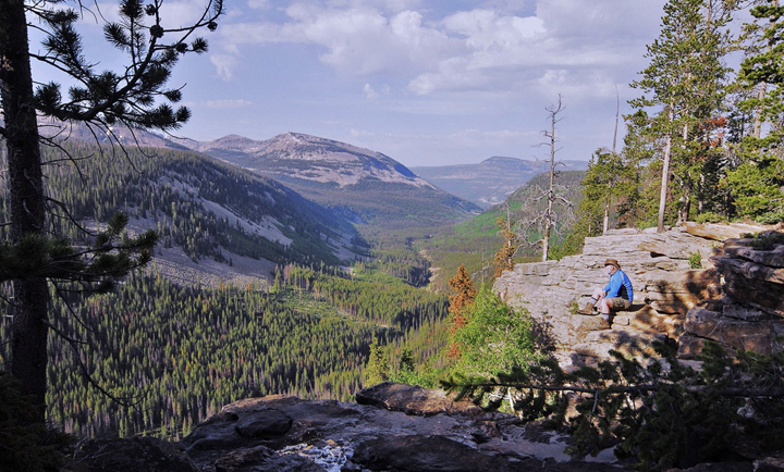 A lone hiker sits on the edge of a large rocky cliff that drops off down to a forest-covered gorge.