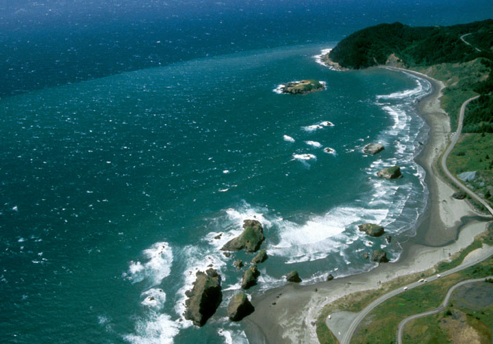 A highway winds along the coast as aquamarine blue ocean swells break upon the nearby beach and rock islands.