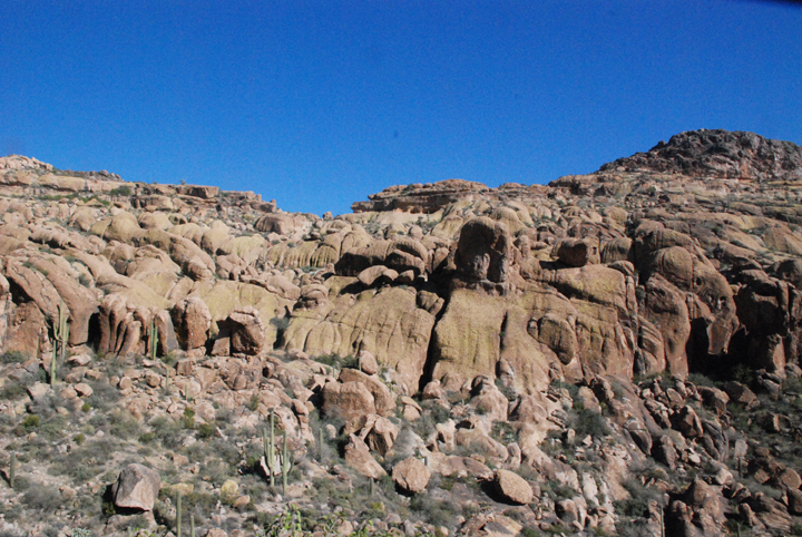A large red rock formation consisting of boulders and stationary rock outcroppings contrasts with the shades of blue sky.