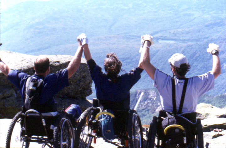 Three men in wheelchairs triumphantly celebrate their ascent by joining and raising hands as they look out over the valley far below.