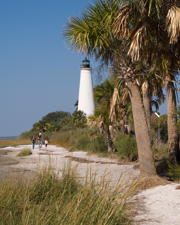 A white lighthouse marks the shoreline, and a group of hikers walk the beach.