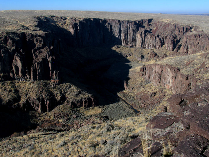 High desert gives way to steep rock cliffs forming a canyon with a river running through the bottom.