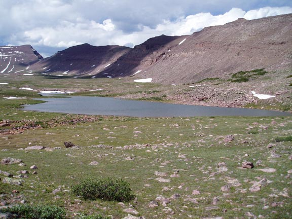 A large alpine pond cradled in a high basin, surrounded by green grass dotted with boulders, at the base of barren ridges on the opposing side.
