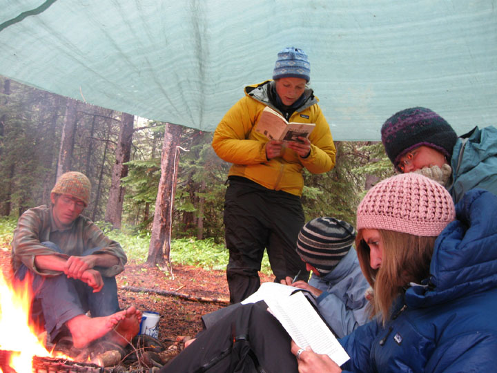 Members of the University of Montana's Wilderness and Civilization Field Studies Fall 2008 Trek commune under a shelter next to a campfire.