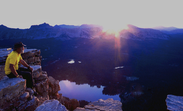 A hiker sits on the edge of a mountain cliff observing the sunrise.