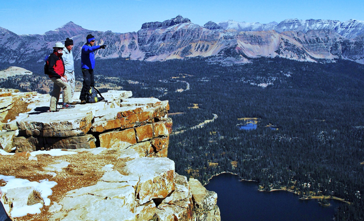 Three hikers stand on the edge of a cliff with a large dark blue lake below and large mountains rising up in the background.