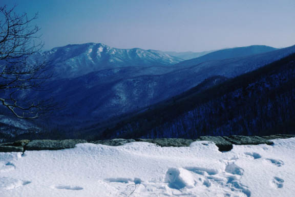 Old Rag Mountain in winter. Footprints in the snow are the foreground of the shot while the mountains are a mix of green and white in the background.