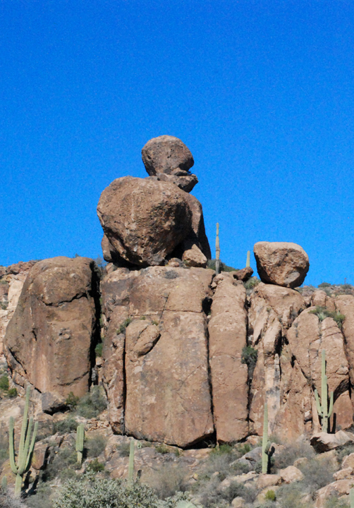 Two boulders (one on top of the other) sit on the edge of a rock outcropping while cacti dot the landscape.