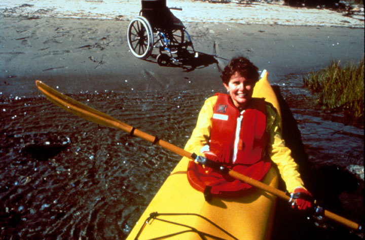 A woman paddles out into the water in a yellow kayak, her wheelchair behind her on the shore.