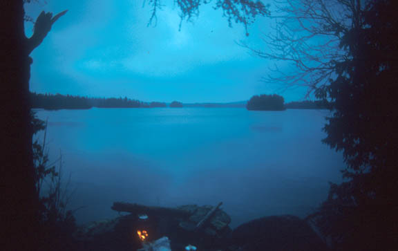 A photo of the Little Saganaga Lake on a cloudy day near sunset, making the entire landscape bluish and gray.