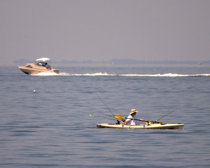 A lone kayaker works his way through still blue ocean water.  In the distance, a speedboat leaves a small wake.