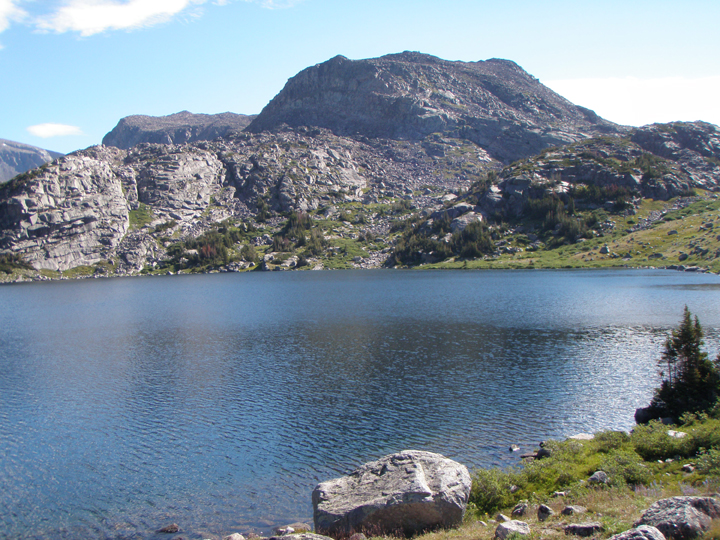 A dark blue lake sits at the base of a large mountain with rocky slopes.