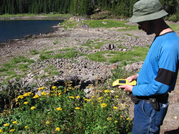 Another volunteer uses a GPS unit near a river in the Rattlesnake Wilderness. This photo was taken during University of Montana summer 2007 volunteer weed inventory study.