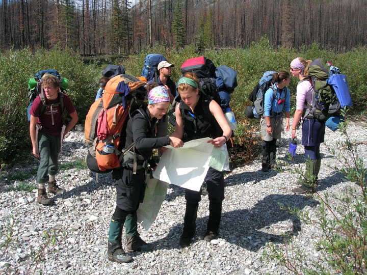 Members of the University of Montana's Wilderness and Civilization Field Studies Fall 2008 Trek carry their gear on their backs and look at a map.