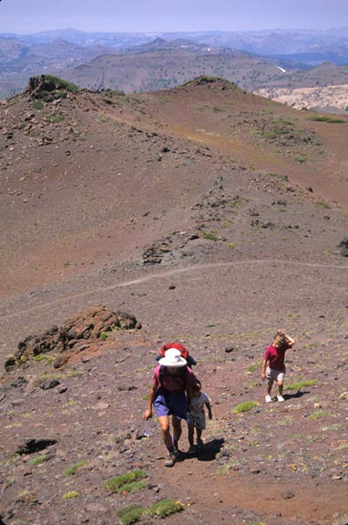 A women and two children hike up a hillside of purpleish-red dirt in the Emigrant Wilderness.