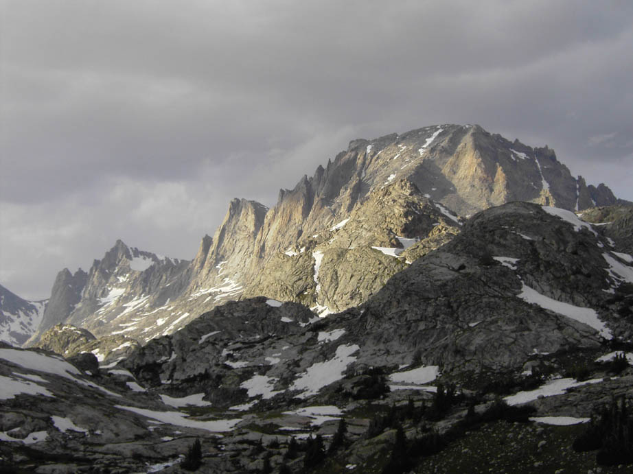 Narrow rays of sunlight illuminating the jagged face of a massive rocky dome in the distance, with dark gray clouds hanging low overhead.