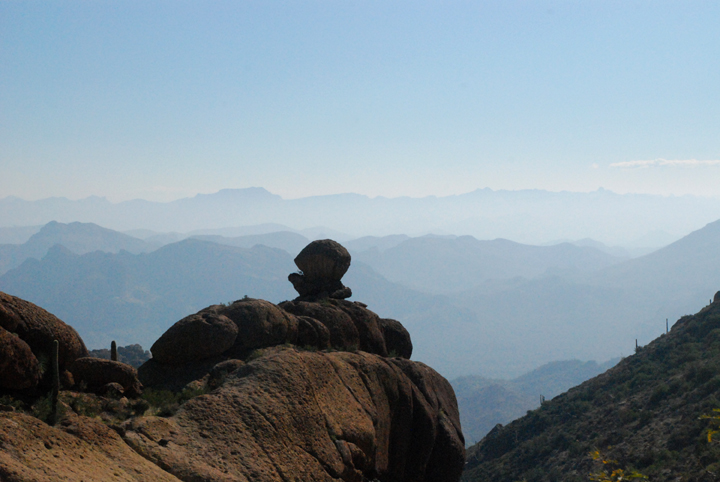Boulders silhouetted against a vision of moutains in the daytime, desert haze.