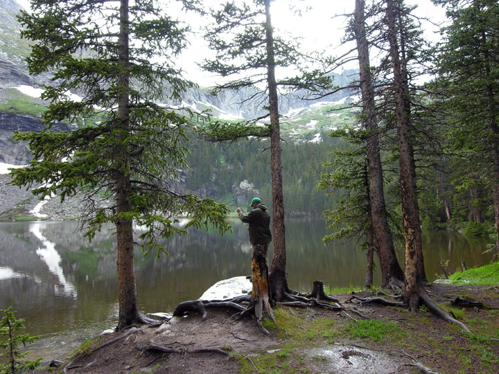 A lone fisherman standing among trees along a mountain lake, vertical peaks rising all around.