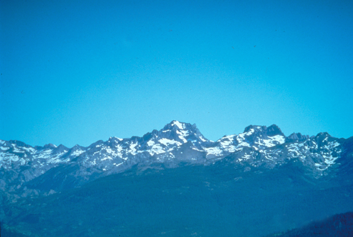 A blue sky meets blue mountains in this scene.  The only true distinguishing feature is the snow that litters the peaks.