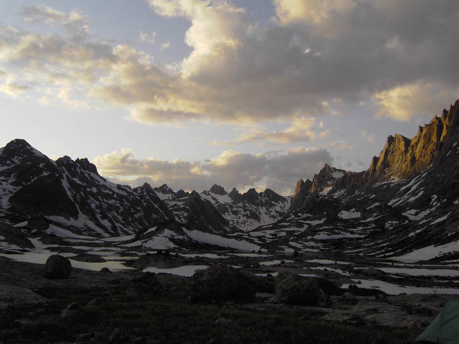 A wide alpine valley surrounded by jagged ridges mottled with late snow, under a golden evening sky.